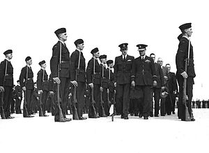Two columns of men, some in military uniforms with peaked caps, some in civilian clothes, walking between two rows of troops with forage caps standing to attention with rifles and fixed bayonets, and further rows of troops behind them