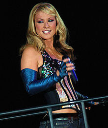 A Caucasian female with blonde hair. The female is wearing a metallic blue glove that covers from above her elbow to her finger tips on both her hands and is holding a microphone with her right hand. She is wearing a shirt with no sleeves that exposes her right hip and she is wearing medium wash jeans. She is smiling with her head slightly turned to her right side.