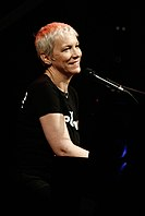Annie Lennox performing on a piano while smiling