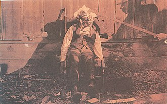Lynching - Body of a lynched black male, propped up in a rocking chair for a photograph, circa 1900. Paint has been applied to his face, circular disks glued to his cheeks, cotton glued to his face and head, while a rod props up the victim's head.