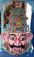 A crowned male wooden head with big eyes and ears, a Vaishnava tilak and bushy brows and moustache. A garland is seen around the neck and on the crown. He has pink skin, and two large canine teeth that hang down lower than his bottom lip. His eyes are wide open and he has large S-shaped ears.