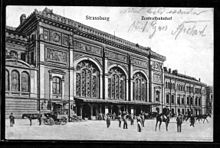 Carte postale montrant partiellement et en perspective la gare de Strasbourg, un imposant bâtiment de style wilhelmien, avec son entrée par la partie centrale et son aile droite. Ses façades, librement inspirées du style Renaissance, s'ouvrent par de grandes baies vitrées. Devant l'auvent de la gare stationnent plusieurs personnes et chevaux attelés ou montés. Les impressions en allemand Strassburg et Zentralbahnhoff figurent au-dessus de la gare parmi d'autres mots manuscrits.