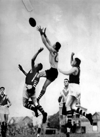Bob Pratt - Bob Pratt leaping for a mark over Richmond ruck-man Bert Foster (11) and in front of full-back Maurie Sheahan (4) at the Lakeside Oval on 9 June 1934.