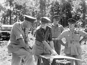 Five soldiers in peaked caps and shirtsleeves study a map on an improvised table in the bush.