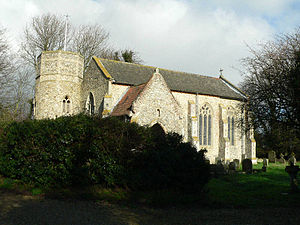 A flint church seen from the southwest.  From the left are a round tower with an octagonal top, the west gable, the south porch, and the south wall of the nave with large windows