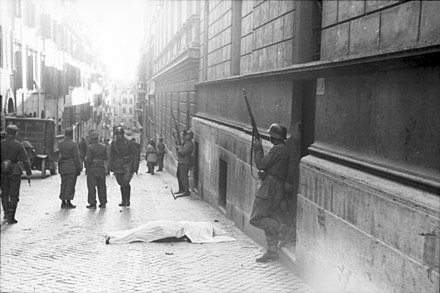 A body lies in the via Rasella, Rome, during the round up of civilians by Italian collaborationist soldiers and German troops after the partisan bombing on 13 March 1944. Bundesarchiv Bild 101I-312-0983-10, Rom, Soldaten vor Gebaude.jpg