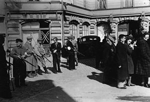 Daugavpils Ghetto - This image, taken in Liepāja, Latvia, in July 1941, shows native Latvians armed and guarding Jews