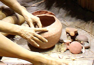 Mississippian culture pottery - A potter smooths the inside of a vessel