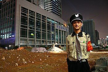 A security officer guards a construction site in the People's Republic of China.