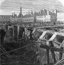drawing showing a large quantity of collapsed brickwork retaining wall and destroyed timber scaffolding alongside a flooded excavation. Beyond the cutting is a wide open area with small figures inspecting the damage. The backdrop is formed by a collection of two storey buildings many of which have large chimneys.