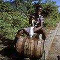 Collectie Nationaal Museum van Wereldculturen TM-20030096 Het vullen van een fles met zoet water uit de ton Sint Eustatius Boy Lawson (Fotograaf).jpg