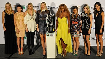 The eight WTA Finals competitors in a line dressed for a formal event, with the tournament trophy in the center