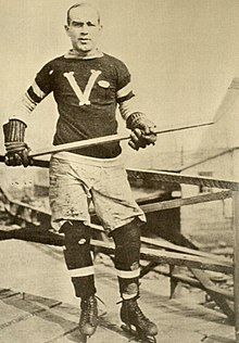 A man poses for a photo wearing skates, an ice hockey sweater and holds a stick in his hands