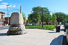 "A large stone block with ""Dana Memorial"" carved into the top and a water basin on the side facing the viewer. It is on a narrow strip of sidewalk in an urban area with a grassy area planted with trees behind it."
