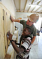 Defense.gov News Photo 110417-N-NY820-518 - Sgt. Peter Swigart and a local child sand newly built cabinets at Trenchtown Primary School in Kingston Jamaica during a Continuing Promise 2011.jpg