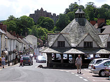 A small single story building with a pyramid shaped roof, to the side of a road lined with buildings. Some private small cars visible. Trees in the distance with the skyline of Dunster Castle.