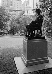 Photo couleur d'une statue d'un homme assis dans un fauteuil