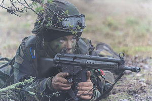Portuguese Armed Forces - A female soldier of the Portuguese Armed Forces in position, with her Hecker and Koch G3 Rifle, during a field exercise
