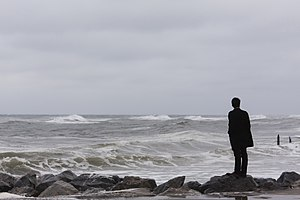 Existential crisis - A man standing alone on the sea shore contemplating meaning in his life and the universe around him.