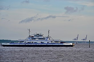 Pleasure Island (North Carolina) - The Fort Fisher Ferry crosses the Cape Fear River returning from Southport.The cranes in the background are part of the US Army's Military Ocean Terminal Sunny Point (MOTSU).