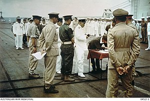 A group of soldiers and sailors parading in various uniforms. In the centre is a small wooden table on which a soldier is signing a document.
