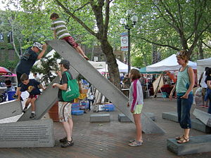 Occidental Park (Seattle) - Children playing on the Firefighters' Memorial in the park on the first Thursday in July 2007. First Thursday is the traditional evening for Pioneer Square art gallery openings. Many artists and craftspeople set up for the evening in the park.
