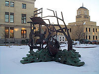 A metal statue showing several people getting into a boat. In the background are several buildings. Snow is seen on the ground.