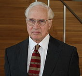 Head and shoulders of a man in his seventies talking into a mounted microphone. He is conservatively dressed in a suite and wears round glasses.