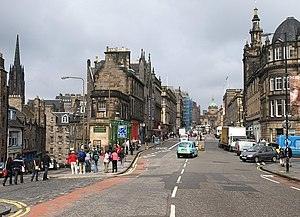 George IV Bridge - George IV Bridge, looking north towards the Royal Mile and, beyond, the coppered-dome of the headquarters of the Bank of Scotland. The junction with Chambers Street is to the right and the crowd on the left surround the statue of Greyfriars Bobby