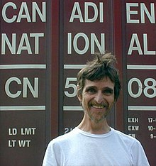 "A man wearing a white t-shirt stands with the words ""Canadien National"" visible behind him."