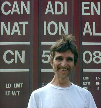 """A man wearing a white t-shirt stands with the words """"Canadien National"""" visible behind him."""