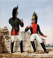 Two French dragoons in green coats with madder red facings, white breeches, brass helmets, and black knee boots
