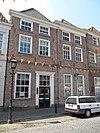 foto van Huis met schilddak en gebosseerd gepleisterde lijstgevel; beganegronds tot winkel samengetrokken met nr 7