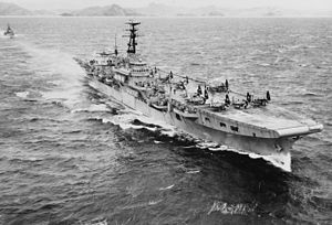 A small aircraft carrier travelling at speed through choppy water. Several propeller aircraft with folded wings are sitting on the flight deck. A small warship is following in the carrier's wake, and a rocky, hilly shoreline can be seen across the horizon