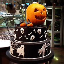 A Halloween cake decorated with ghosts, spider webs, skulls and long bones, jack-o'-lanterns and spiders. The cake is topped with a jack-o'-lantern