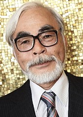Close up photograph of Hayao Miyazaki, smiling and wearing a suit and tie in front of a gold-colored mosaic.