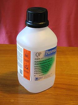 "White plastic bottle with safety cap is labeled ""QP Panreac"" above smaller text ""Hydrofloric Acid 40% QP"" with 6 translations. In a bright orange region along the side, warning symbols are clearly visible."