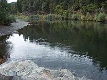 Una vasta placido fiume scorre attraverso i boschi.