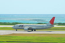Un 737-400 aircraft painted in Japan Transocean Air livery, travelling along the runway during take-off, with a clear green grass strip in the foreground and a blue sea view in the background