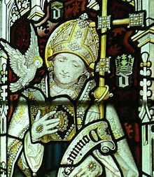 "A man in white robes wearing a mitre, reading a book in his right hand; alongside him, a cross; robes, mitre, book and cross are encrusted with jewels. On his right shoulder, a dove with a halo. In the background, golden crowns over a stylised letter ""d"""