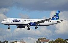 """Un aereo bianco con le parole """"jetBlue"""" dipinte nella parte anteriore e una pinna caudale blu-verde si avvicina all'atterraggio con il carrello di atterraggio dispiegato mentre si libra sopra le case sottostanti"""