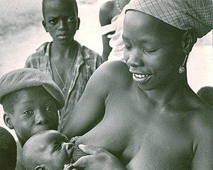 Breastfeeding in public - A new mother in Kabala, Sierra Leone in West Africa nurses outdoors.