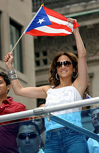A middle aged, brown-haired woman, wearing brownish glasses, white T-shirt and blue jeans, waves the flag of Puerto Rico.