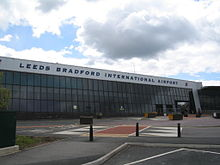 "The frontage, consisting mainly three rows of glass panes, of a long building. Above the glass is a concrete section containing the words ""Leeds Bradford International Airport"" in capitals and, to the right, an aeroplane symbol. Beyond this, the concrete section continues diagonally downwards to the ground. To the left of this support is an entrance which cuts into six panes of the two lower rows of glass panels, and some passengers pulling suitcases are entering the building. Two smaller entrances to the left replace four of the ground-level panels. In front of these are railings. In the foreground are roads, pedestrian walkways, bollards and five large free-standing box-shaped objects."