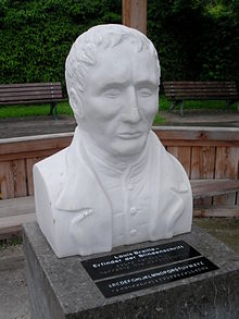 "In a park, two benches in the background.  A Brailles bust made of snow-white marble stands on a base made of dark gray granite.  He wears a coat with a large collar, including a vest with a stand-up collar.  His wavy hair falls forward in strands, his deep-set eyes are almost completely closed.  He has strong cheekbones and narrow lips - this makes his features look a little hard.  On the pedestal in front of the bust, there are two black writing boards that are written on the top in normal white letters and below in Braille.  The upper one reads ""Louis Braille - the inventor of Braille"", the lower one shows the alphabet in normal and braille."