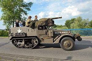 Several men and women riding a preserved M9 Half-track with a U.S. Army re-enactor.