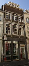 foto van Huis met lijstgevel, met gekoppelde segmentboogvensters in Naamse steen