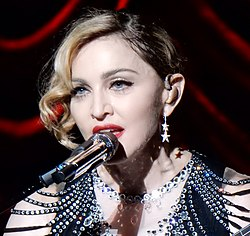 Madonna in a bejeweled dress in front of a microphone
