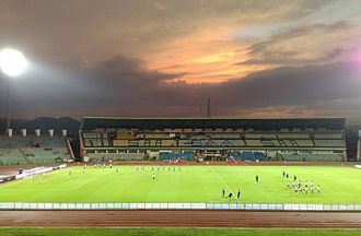 Indira Gandhi Athletic Stadium - The Main Stand of the Indira Gandhi Athletic Stadium in the background while the players of the Indian National Football team and the Laos National Football team warm-up under the floodlights.