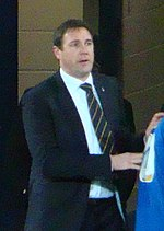 The head and torso of a man in his 30s or 40s, wearing a shirt, tie and blazer.
